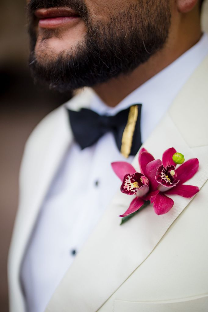orchid boutonnieres on the groom