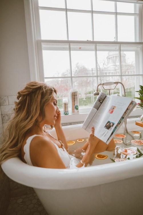 girl enjoying its me time in a bathtub reading magazine