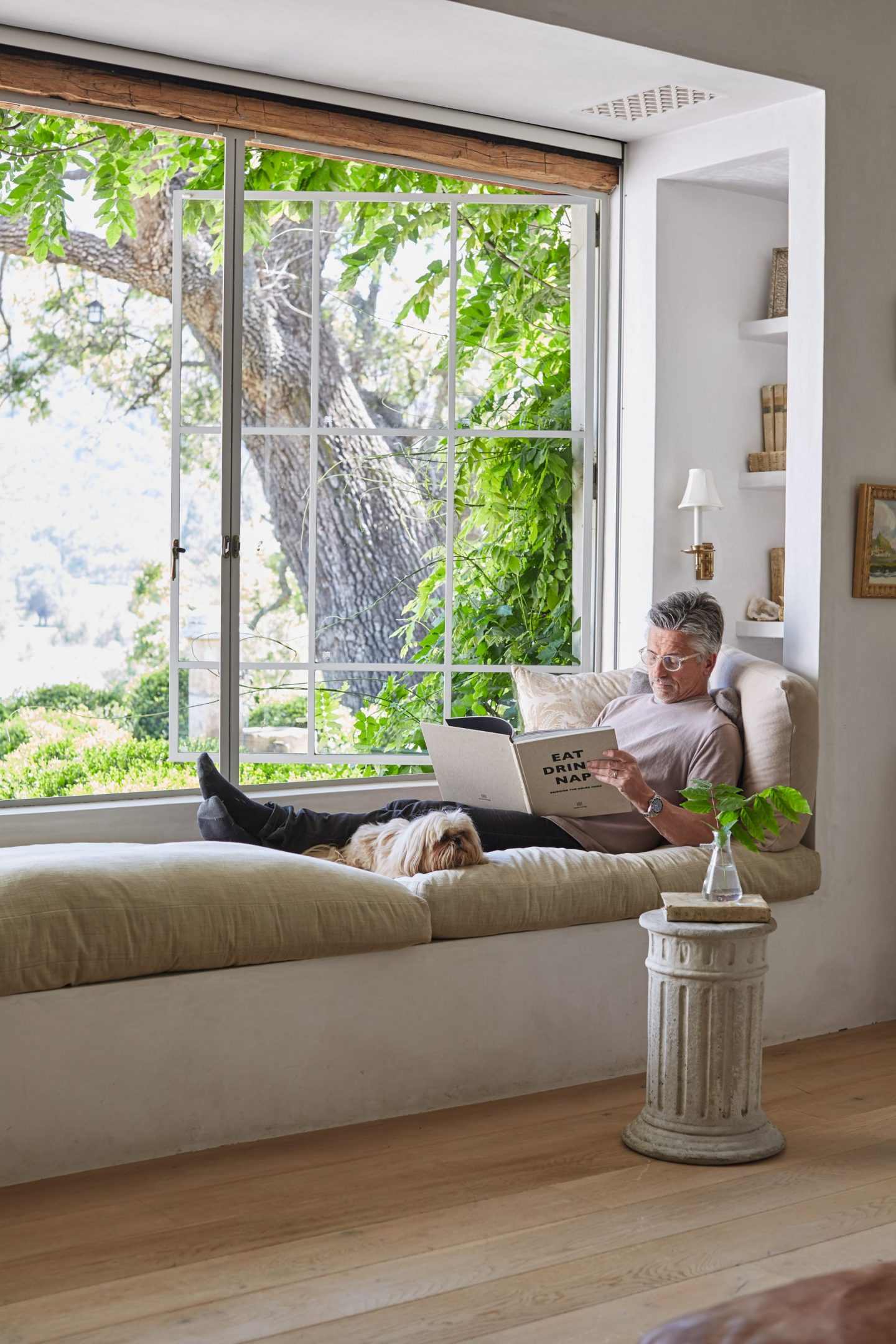 Patina Living photo of Steve Giannetti with Sophie on built-in window seat bench at Patina Farm. Photo by Victoria Pearson. #patinafarm #stevegiannetti #windowseat #europeancountry #interiordesign #modernfarmhouse