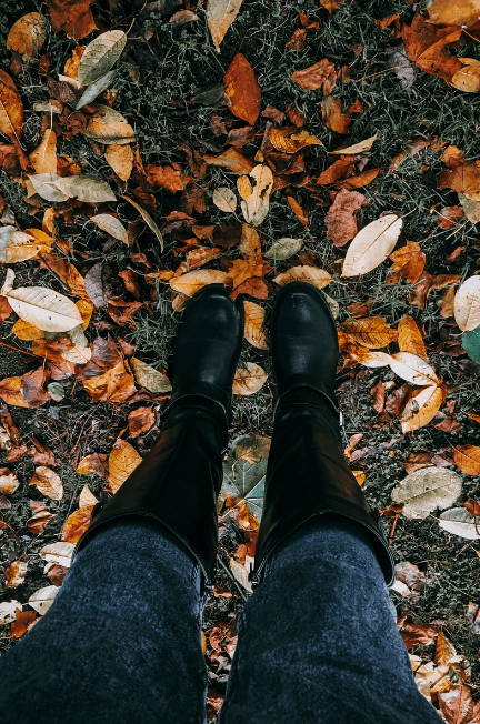 The overhead view of tall boots over fall leaves on the ground.