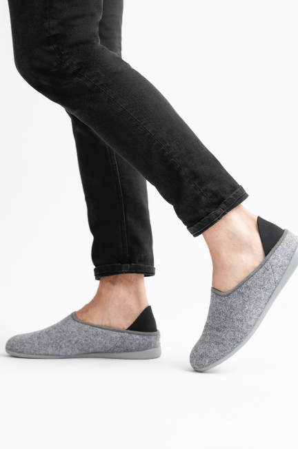 Legs with black pants on them, wearing great slippers