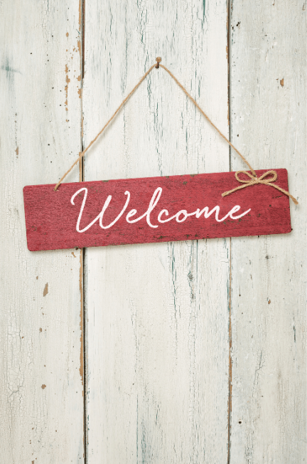 red wood welcome sign in front of a white board image