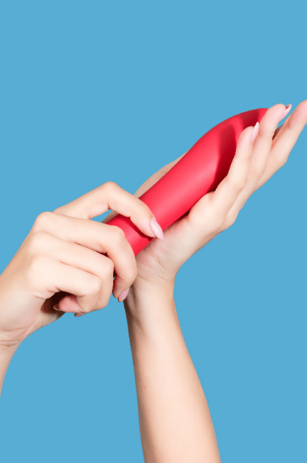 hands holding a pink vibrator against a light blue background
