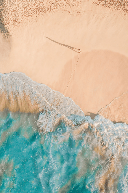 An overhead shot of a clear beach with one person on it