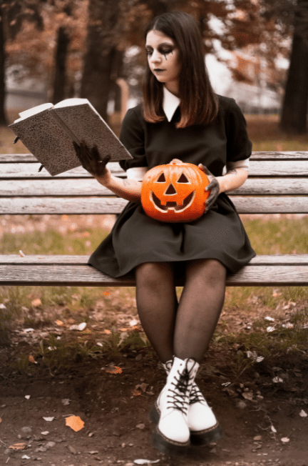 Woman dressed as Wednesday Addams reading on a bench.