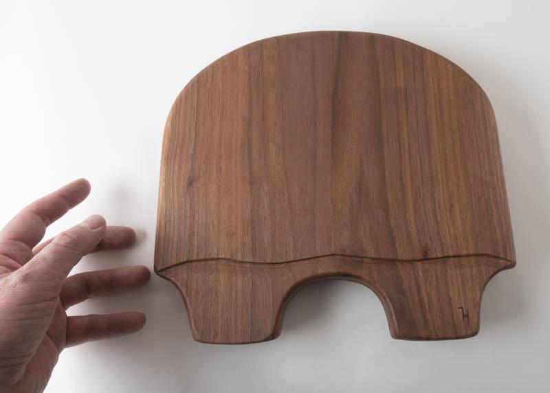 Hand reaching for Turtle Charcuterie board, in walnut