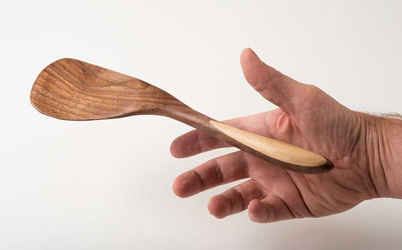Hand reaching for a Paddle Spatula, in cherry and birch