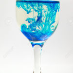 Glass full of water with ink color drop