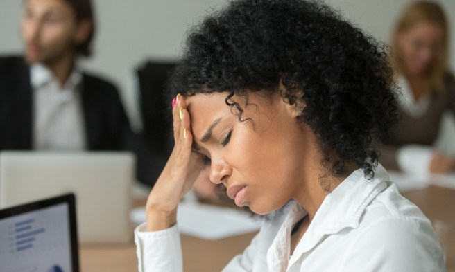 Young woman in office hand to forehead