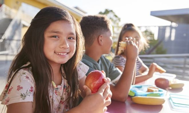 girl with apple sits with schoolmates 768 - HEALTH AND FITNESS