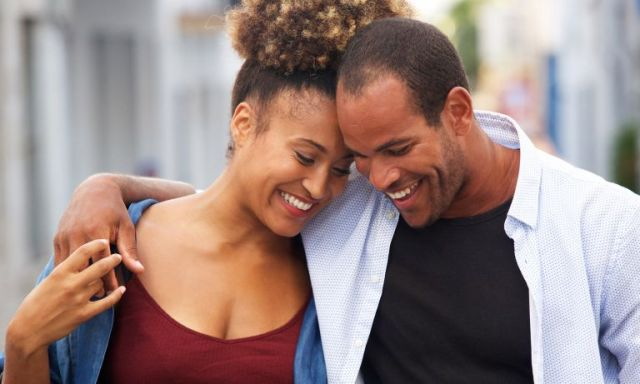 Man with arm around woman, walking down the street as they lean into each other smiling