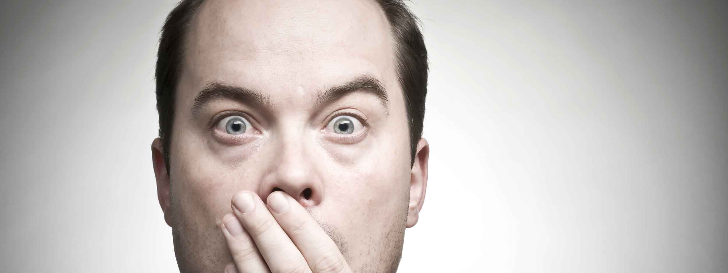 Man covering his mouth in shock after learning more about Tinnitus