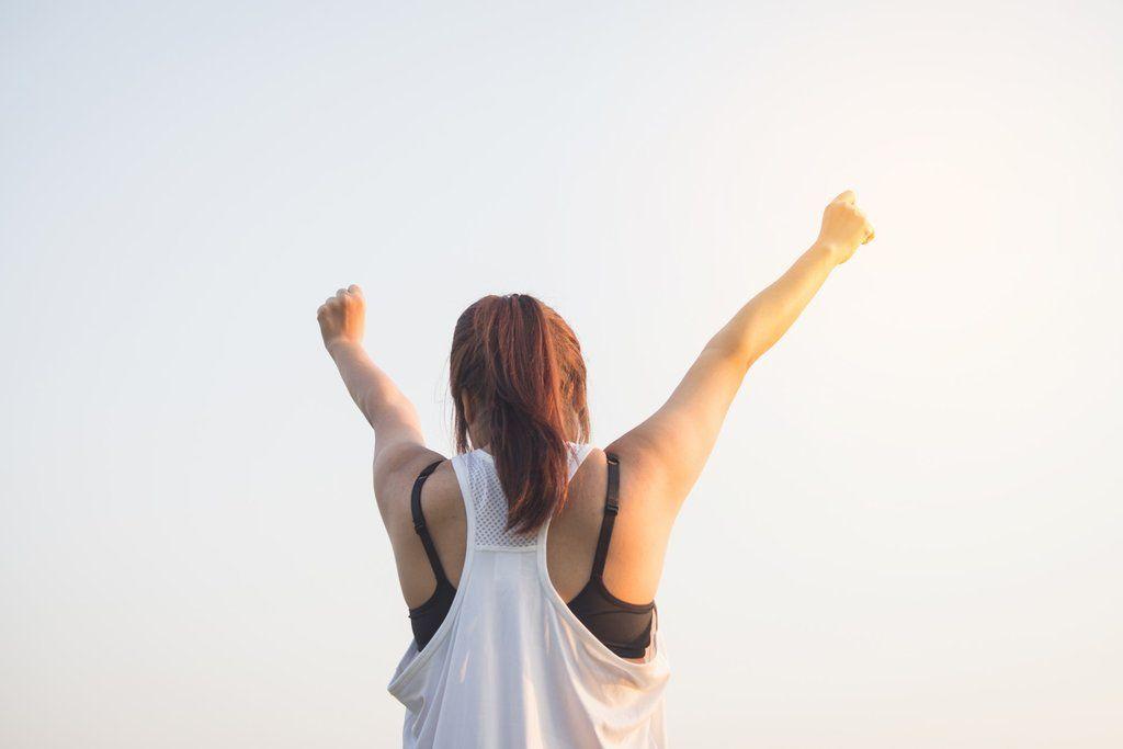 femme-qui-lève-les-poings-en-l-air-en-signe-de-victoire