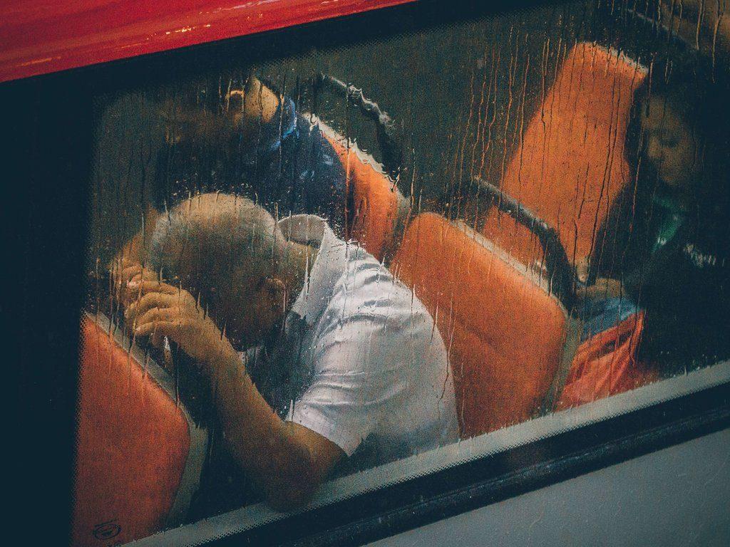 homme déprimé dans un train la tête appuyé sur le fauteuil devant lui