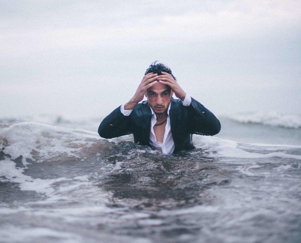 hommes-oucieux-en costume- debout-dans-l-eau-se-tenant-la tete