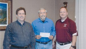 Henderson Community Foundation President Norm Yoder was presented with a check for the Henderson Community Foundation Scholarship Fund from Henderson State Bank, represented by Kevin Postier and JB Suddarth.