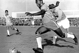 Pelé dribbling past a defender while playing for Brazil, May 1960.