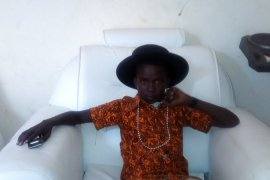 Prince Yubu reclines on white couch