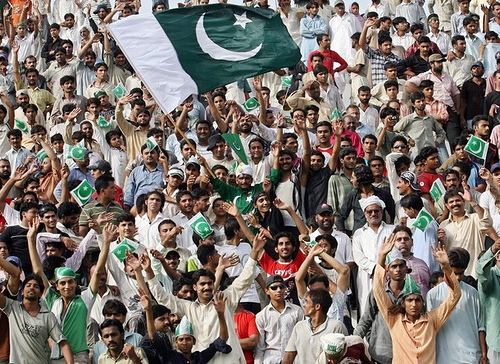 Pakistani people wave national flags during a presentation of sweets from the Pakistani Rangers to the Indian Border Security Force to celebrate Pakistan's Independence Day at the Pakistan-India border at Wagah, 14 August 2007. Pakistan celebrated the 60th anniversary of independence on Tuesday with prayers and a national minute of silence, low-key festivities for a country in the grip of political and religious turmoil. AFP PHOTO/Arif ALI (Photo credit should read Arif Ali/AFP/Getty Images)