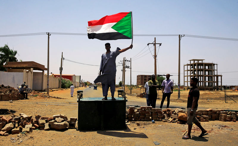 A Sudanese protester holds a national flag as he stands on a barricade along a street, demanding that the country's Transitional Military Council hand over power to civilians, in Khartoum, Sudan June 5, 2019. REUTERS/Stringer