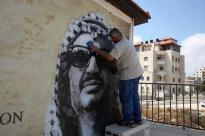A man cleans a portrait of the late Palestinian leader Yasser Arafat