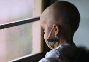 Pediatric cancer survivor looking out the window