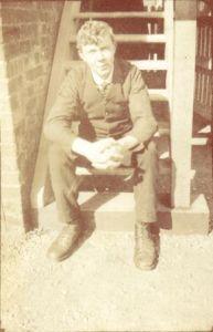 Gerard Oldfield Stills in railway uniform, seated on the steps of Surfleet Seas End signal box