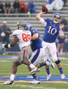 Kansas quarterback Dayne Crist throws as fullback Nick Sizemore fends off Oklahoma State defensive end Nigel Nicholas during the second quarter on Saturday, Oct. 13, 2012 at Memorial Stadium. (Nick Krug / Lawrence Journal-World)