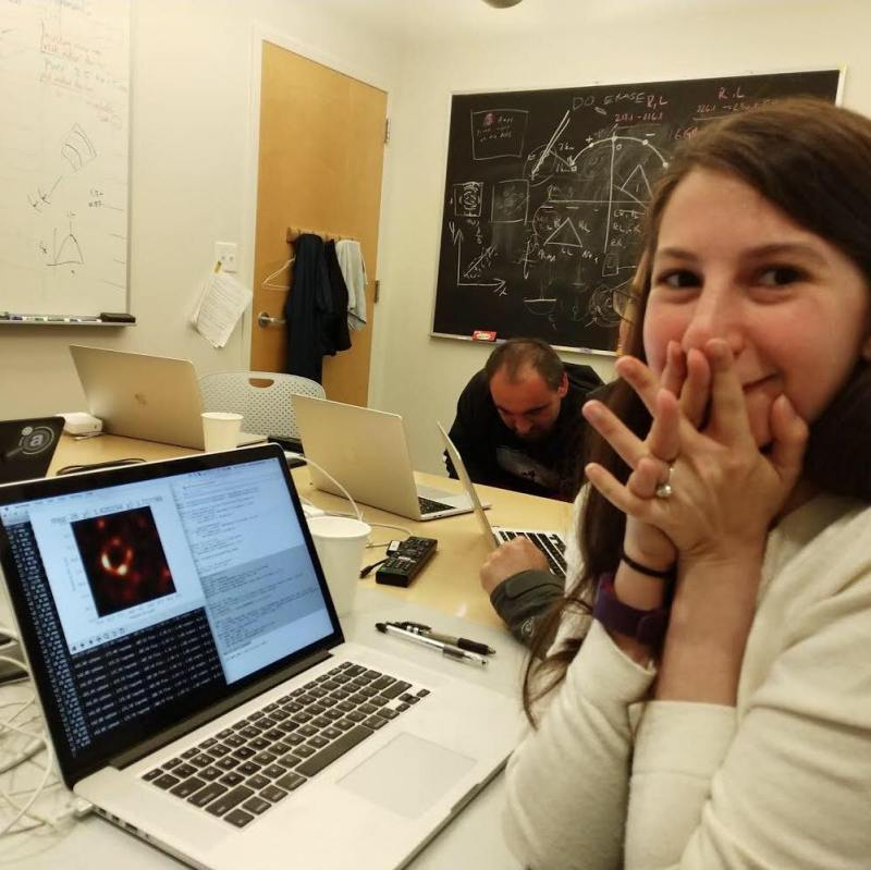 Dr. Katie Bouman watches the first ever photo of a black hole render on her laptop.