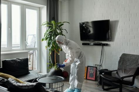 a man spraying a table in special protection gear