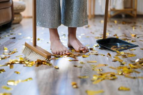 A person holding a broom among gold confetti.
