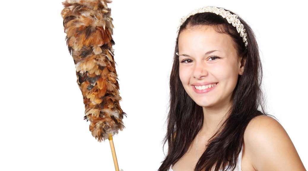A girl in white holding a feather duster.