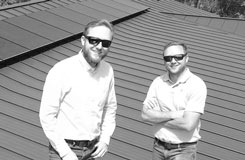 black and white photo of owners eric and derrick hoffman standing in front of solar panels