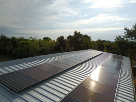 2 separate rows of panasonic solar panels on a metal building in Bastrop TX