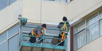 Workers cleaning windows and painting the outside of a sky scraper.
