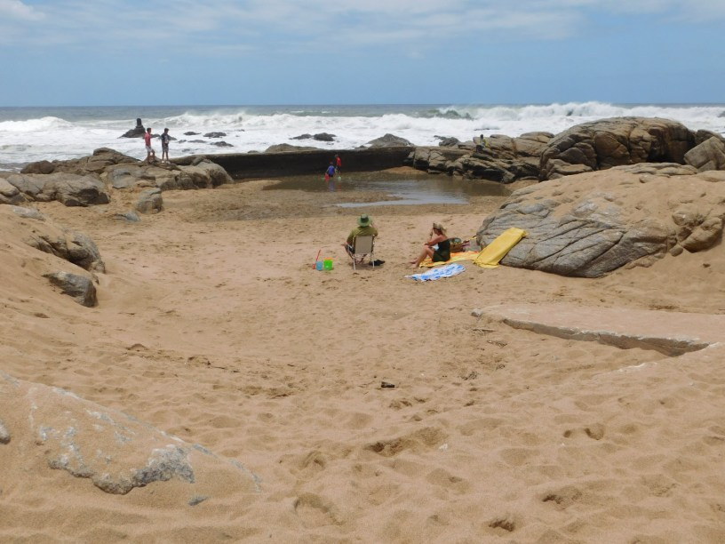 Holidaymakers camping out in the empty tidal pool