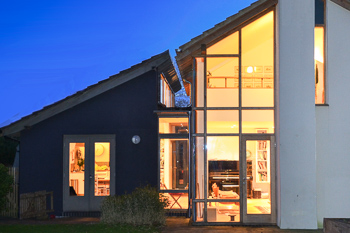 Image of the rear of the house at dusk showing how the large split-level garden extension visually and spatially links via a glazed corner.