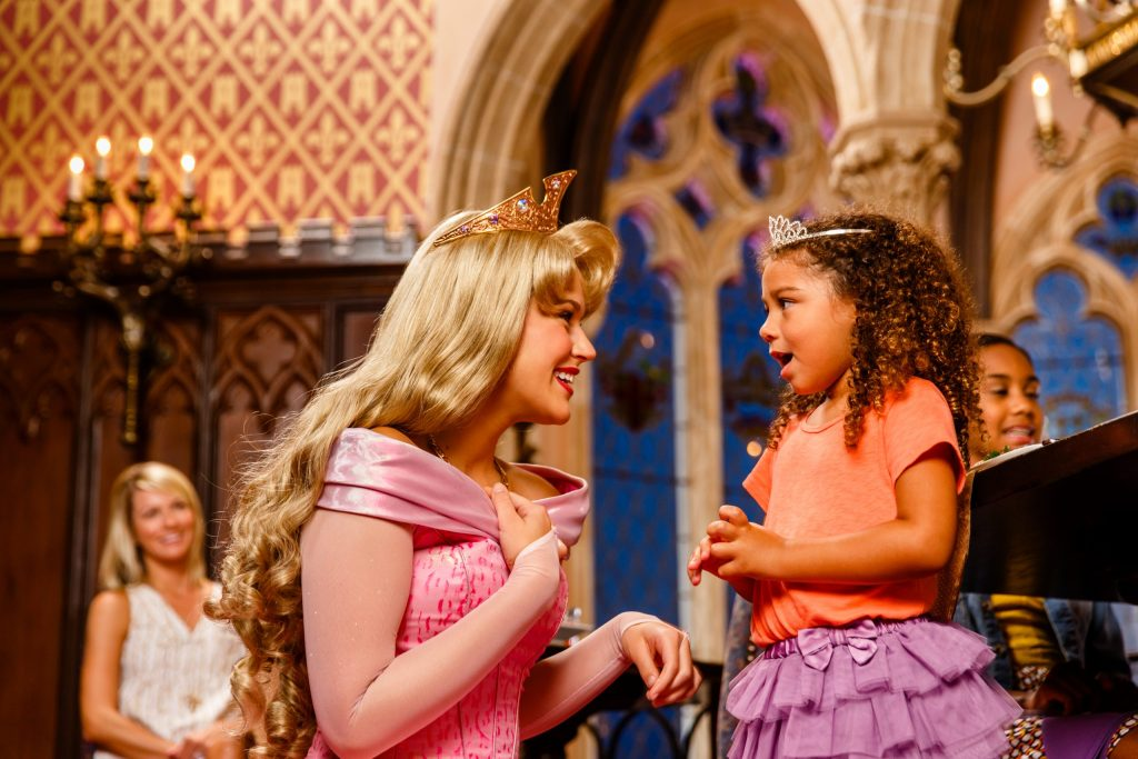 Little girl with tiara on her head stands in shock as she meets Princess Aurora