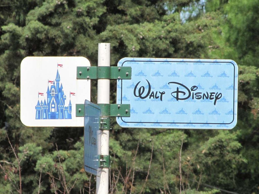A sign post has 3 signs, one says Walt Disney and one says Mickey and one has a castle on it.
