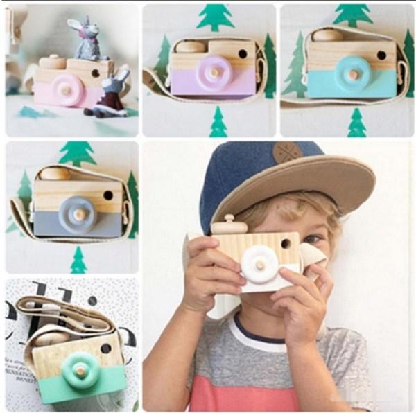 Enfant garçon qui joue avec un appareil photo en bois