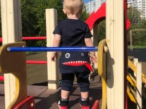 Bébé avec son pantalon de survêtement dans le parc pour enfants