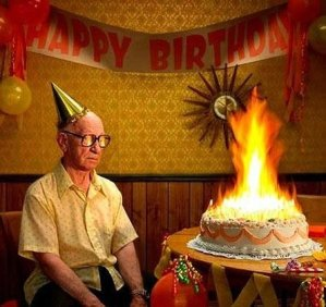 Old man birthday cake: An old man looking unamused while a birthday cake sits in front of him with so many candles the cake is alight.