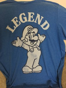 Super Mario Tee: A t-shirt depicting a black and white picture of Mario holding his hands in the air. Above is the text 'Legend' in white caps.