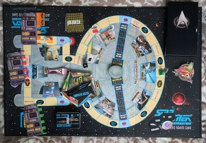 A shot from above of the Star Trek: A Klingon Challenge playing board with the Enterprise 1701D from above. Various game cards are placed on the board.