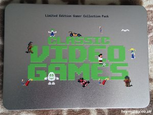 The lid of the presentation tin for the video game stamps. The words 'Classic Video Games' are displayed in a classic, green retro computer style font. Various sprites from the games depicted are shown around the text.