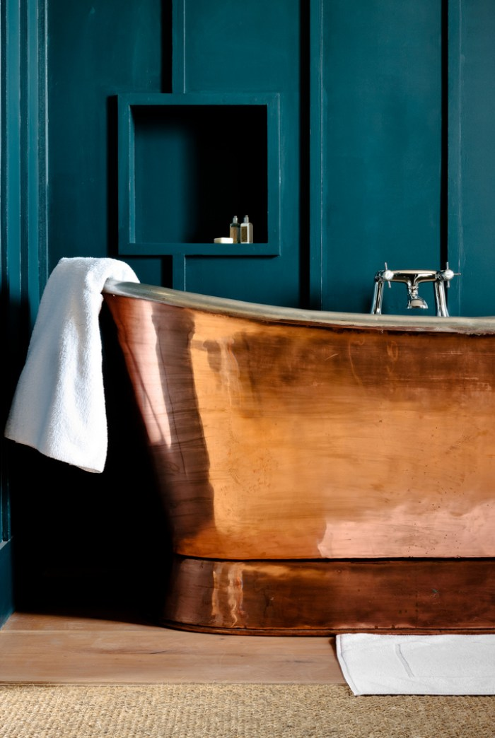 Teal bathroom with copper bathtub