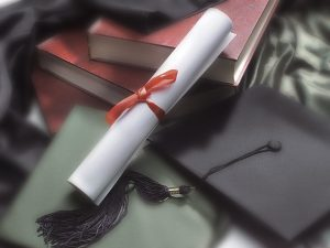 a diploma with a red ribbon and a graduation cap next to two red books on a table