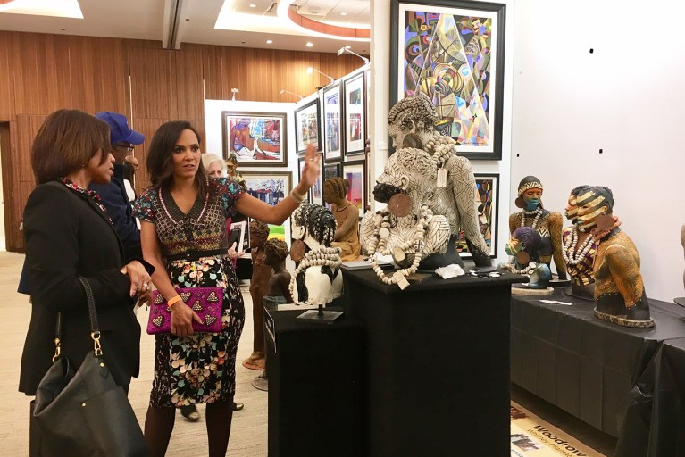 Guests discussing art and sculptures at the Woodrow Nash exhibit booth