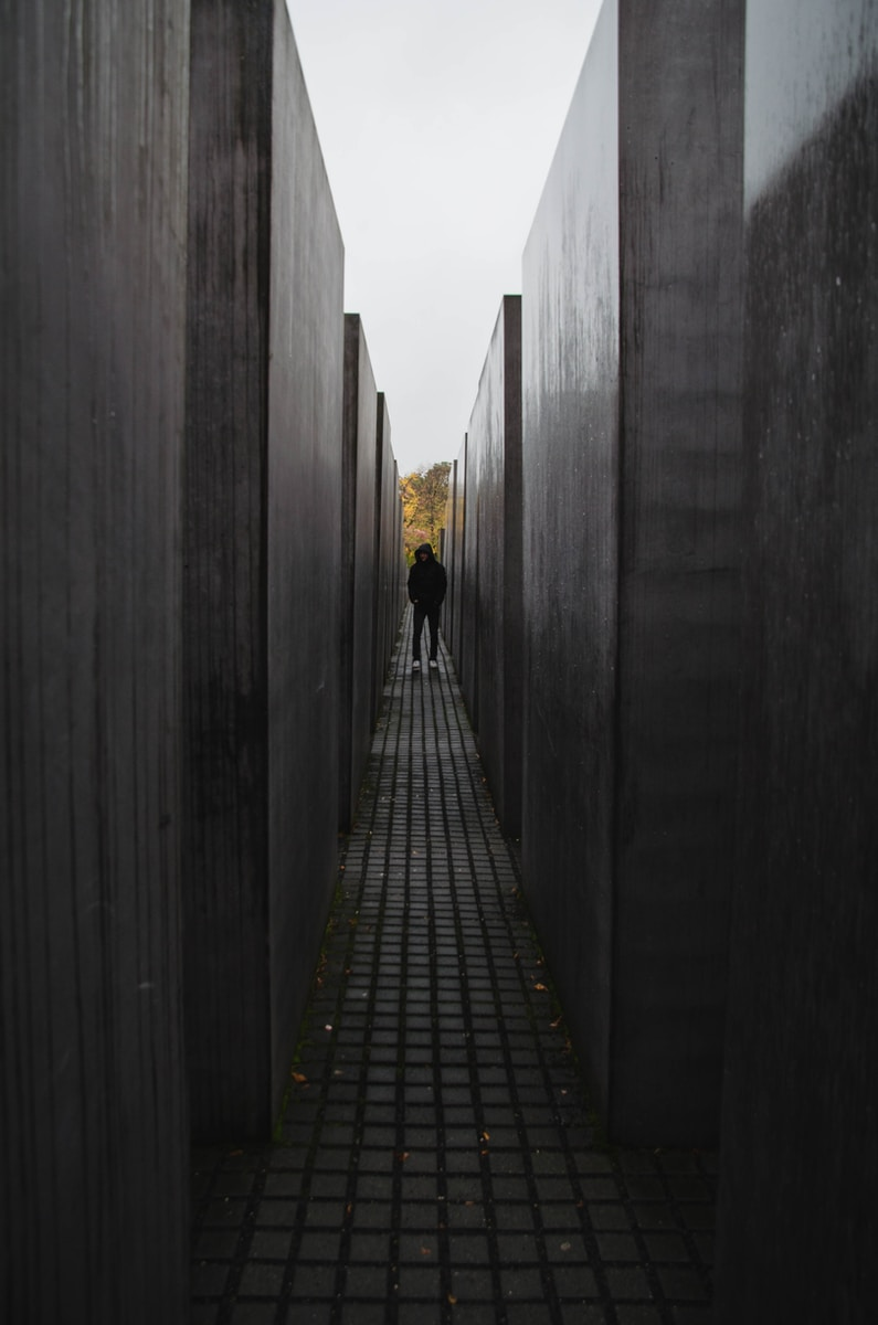 black and white wooden pathway between gray concrete walls