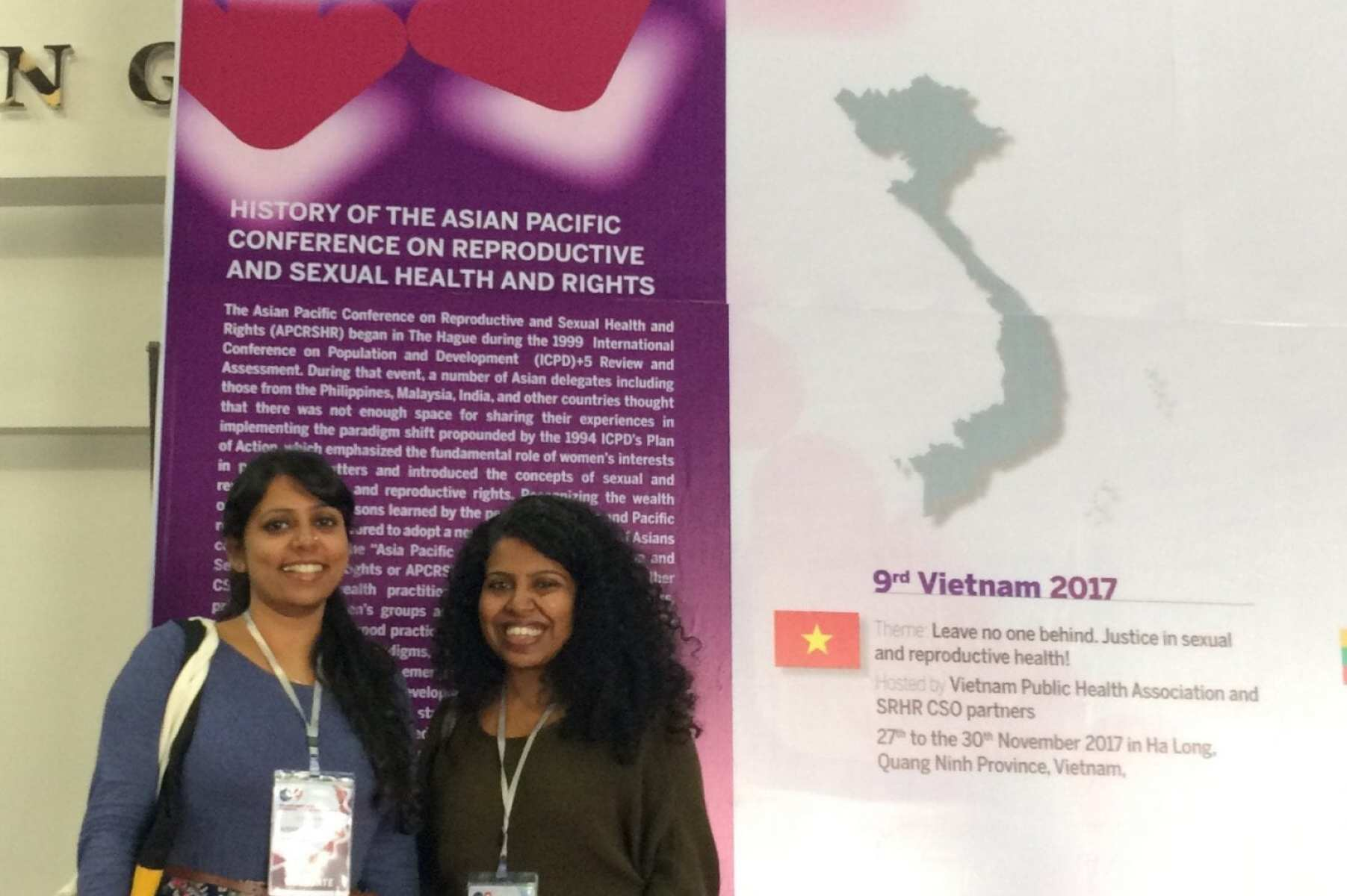 2 women standing in front of poster about APCRSHR9